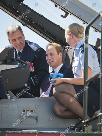 Prince William sits in the cockpit of an F/A-18F Super Hornet while Chief of Air Force, Air Marshal Geoff Brown, AO and Flight Lieutenant Jasmine Richards explain some of its features