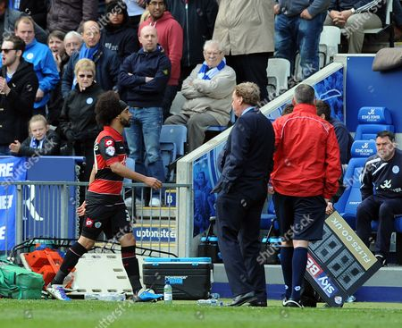 Benoit Assou-Ekotto of QPR walks past manager Harry Redknapp after being shown the Red card