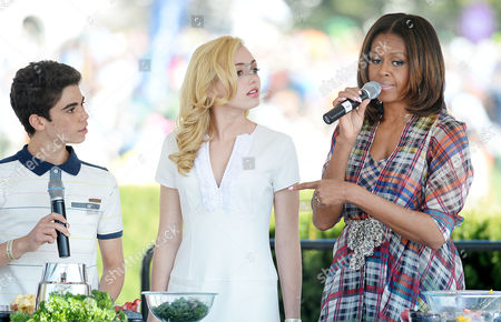 United States first lady Michelle Obama (R) makes a healthy drink with comedian Peyton List and Cameron Boyce (L) during the annual White House Easter Egg Roll.