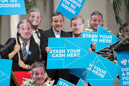 Protesters wearing masks featuring the face of Barclays boss Antony Jenkins protest against Barclays helping businesses set up in tax havens outside Royal Festival Hall