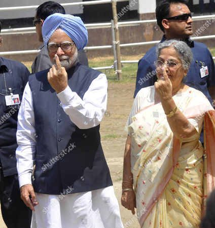 Stock Image of Prime minister of India Dr Manmohan Singh and his wife Gursharan Kaur show ink mark finger after casting their vote in a polling station at Dispur Government Higher Secondary School in Guwahati