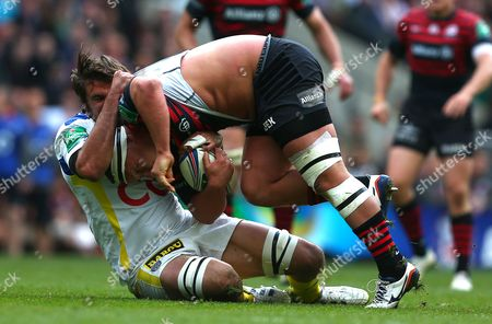 Jamie George of Saracens is tackled by Julien Pierre of ASM Clermont Auvergne