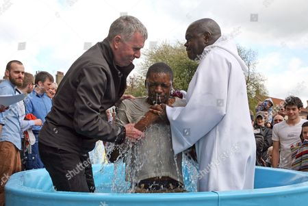 Victor Ekpo, from the Elim Pentecostal Church in York is baptisedby the Archbishop of York, Dr John Sentamu with Minister Graham Hutchinson (L) assisting