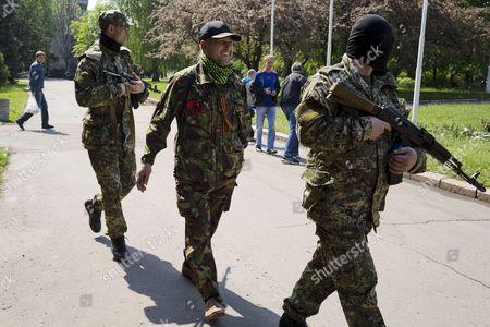 Self declared mayor Vyacheslav Ponomarev (C) walks back to the seized town hall of Sloviansk