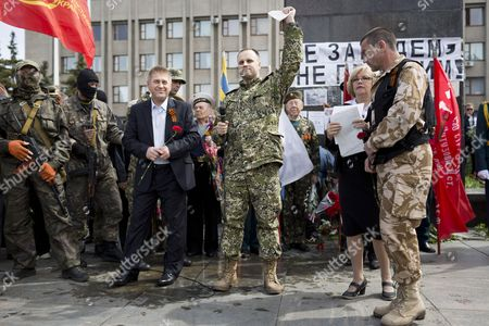 Stock Photo of Residents of Sloviansk commemorate Victory Day on Lenin square in Sloviansk . Self proclaimed mayor Viacheslav Ponomariov (CL) and Donetsk people governor Pavel Gubarev (CR) appear during the commemoration