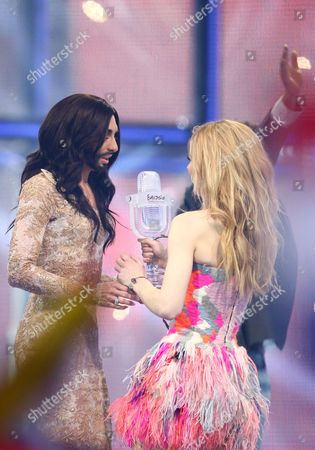 Stock Photo of Conchita Wurst of Austria wins the Eurovision Song Contest 2014 and recieves the trophy from last years winner Emmelie de Forest.