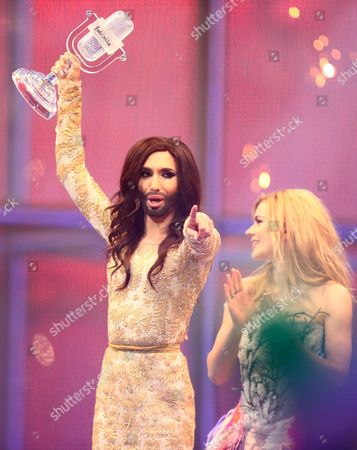Conchita Wurst of Austria wins the Eurovision Song Contest 2014 and recieves the trophy from last years winner Emmelie de Forest.