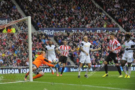 Gerhard Tremmel of Swansea City (L) makes a save from a Sunderland attack