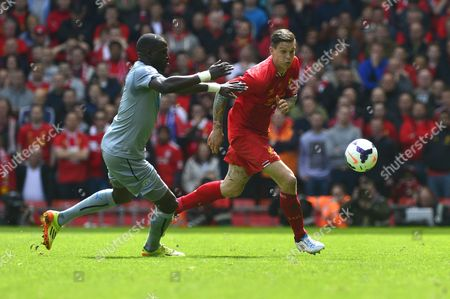 Liverpool's Daniel Agger competes with Newcastle United's Moussa Sissoko