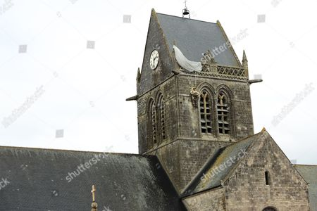 Stock Photo of Sainte-Mere-Eglise churchwith parachute and dummy paratrooper representing John Steel who became trapped on the church on D Day, Normandy, France