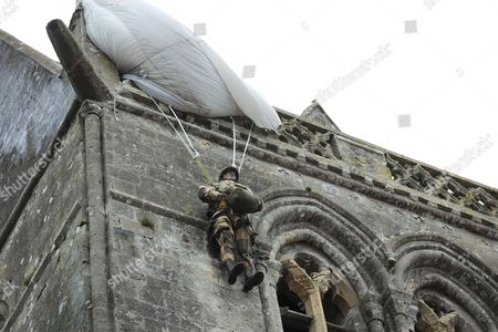 Sainte-Mere-Eglise churchwith parachute and dummy paratrooper representing John Steel who became trapped on the church on D Day, Normandy, France