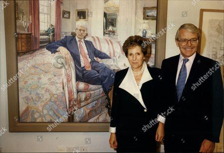 Prime Minister John Major & Wife Norma Major Standing In Front Of Painting Of John Major By John Wonnacott At The National Portrait Gallery.