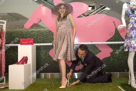 Laura Coleman tries on some stilettos while head of personal styling Alain Mehada measures how much they sink into the grass