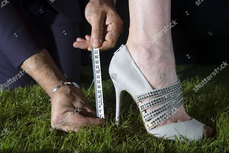 Stock Photo of Laura Coleman tries on some stilettos while head of personal styling Alain Mehada measures how much they sink into the grass