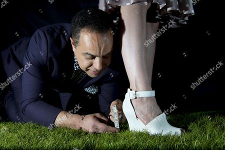 Stock Image of Laura Coleman tries on some wedges while head of personal styling Alain Mehada measures how much they sink into the grass