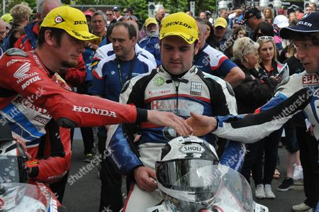 Connor Cummins and Guy Martin shake hands over Michael Dunlop in park ferme after the Senior race