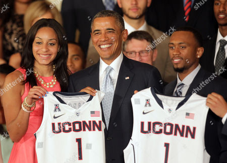 President Barack Obama receives a jersey from Bria Hartley and Ryan Boatright of the University of Connecticut women's and men's basketball teams