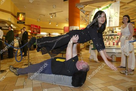ROY SINGFIELD HOLDING HIS ASSISTANT WHILE LYING ON A BED OF NAILS