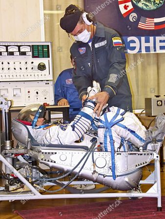 Baikonur, Kazakhstan, September 18, 2006, a Russian specialist checks the spacesuit of first female space tourist anousheh ansari before the launch of Soyuz tma-9 rocket, which spacecraft is to take the 14th ISS crew to the international space station.