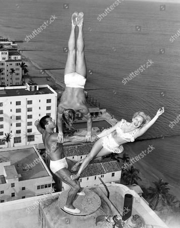 Miami Beach, Florida: November 15, 1951 The Wayne-Marlin trio rehearses atop the chimney of the Lord Tarleton Hotel. George Wayne Long holds Glen Marlin Sundby and his sister Dolores with no apparent effort twenty stories above the ground.