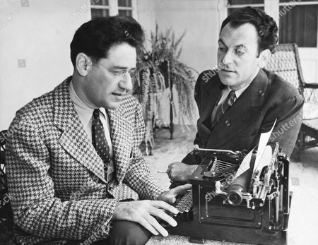 United States: May 6, 1937 Noted playwrights George S. Kaufman and Moss Hart with Kaufman at a typewriter. The two men collaborated on numerous plays.