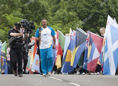 Daley Thompson carrying the Commonwealth Games baton over the border