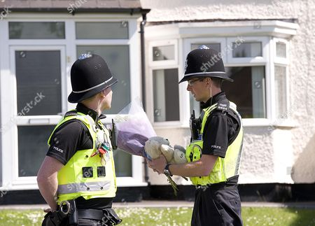 A Policeman Takes Some Flowers And A Teddy At The Scene At Chells Grove Billesley West Midlands Where A Young Mother Yvonne Walsh And Her 9 Month Old Son Harry Were Found Murdered. (3/06/13).
