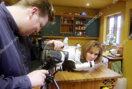 Stock Photo of NIKKI NUTLEY BEING FILMED BY HUSBAND DAVID ON THE KITCHEN TABLE