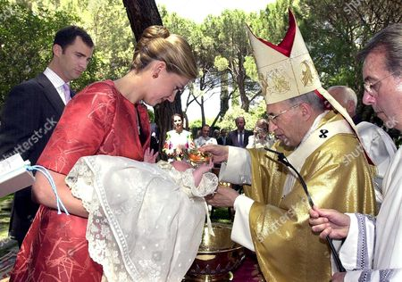 PRINCE MIGUEL IS BAPTISED BY ANTONIO MARIA ROUCO VARELA, ARCHBISHOP OF MADRID. HE IS HELD BY MOTHER PRINCESS CRISTINA AND THE CEREMONY IS WATCHED BY GODFATHER PRINCE FELIPE (L)