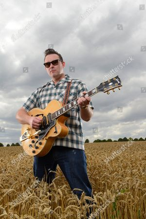 Reading United Kingdom - August 6: Portrait Of English Rock Musician Darrel Higham Guitarist With Irish Rock And Blues Performer Imelda May Photographed In A Wheat Field Near His Home In Reading England On August 6