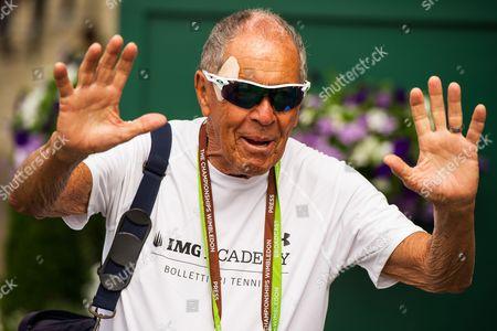 Nick Bollettieri waves as he walks around Wimbledon on Day One of the 2014 Wimbledon Championships