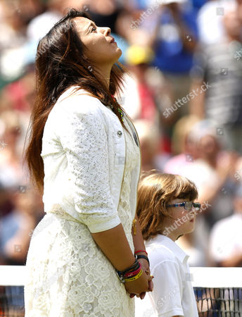 Stock Picture of Marion Bartoli walks onto court in tears as defending Champion with a kid from the Elena Baltacha Academy during Wimbledon, 2014