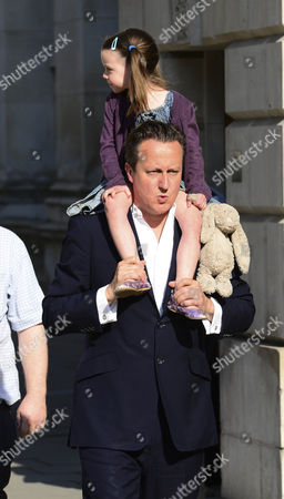 David Cameron carries his daughter Florence Cameron on his shoulders as she clutches her stuffed rabbit toy