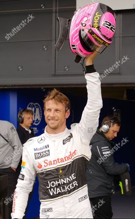 Stock Picture of British driver Jenson Button celebrates qualifying third, with his special pink helmet in tribute to his father John Button