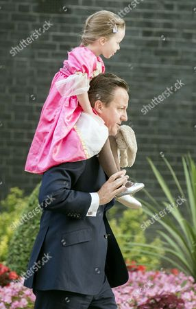 Prime Minister David Cameron carries his daughter Florence Cameron on his shoulders on their way to her nursey school