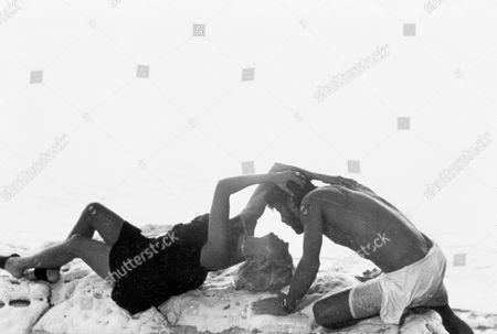 FILM STILLS OF 'SWEPT AWAY' WITH 1975, BEACH, CLOTHING, EMBRACE, GIANCARLO GIANNINI, MARIANGELA MELATO, ROMANCE, TATTERED CLOTHING, LINA WERTMULLER IN 1975