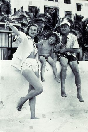 FILM STILLS OF 1954, LAUREN BACALL, BATHING SUIT, BATHING TRUNKS, BEACH, HUMPHREY BOGART, STEPHEN BOGART, CHILDREN, CLOTHING, FAMILIES (REAL), HAWAII, PARENTS & SON, VACATIONING, VACATION, POINTING, SWIM SUIT, CHILD, MARRIED COUPLES, SON, OUTDOORS IN 1954