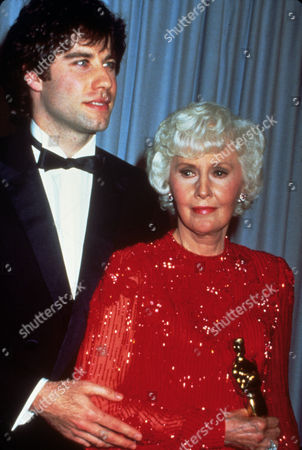 FILM STILLS OF AWARDS - OSCARS, 1981, ACADEMY AWARDS CEREMONIES, ACCESSORIES, AWARDS - ACADEMY, DOROTHY CHANDLER PAVILION, HONORARY AWARD, OSCAR (ACADEMY AWARD STATUE), BARBARA STANWYCK, JOHN TRAVOLTA, HOLDING AWARD, OSCAR RETRO, OSCAR (PERSONALITY) IN 1981