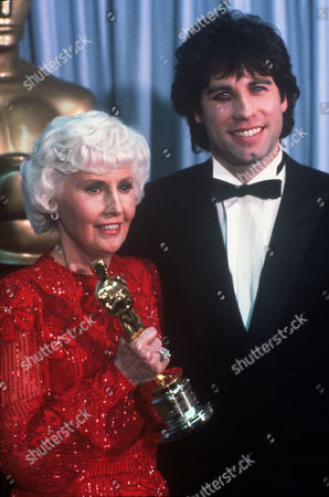 FILM STILLS OF AWARDS - OSCARS, 1981, ACADEMY AWARDS CEREMONIES, ACCESSORIES, AWARDS - ACADEMY, DOROTHY CHANDLER PAVILION, HONORARY AWARD, OSCAR (ACADEMY AWARD STATUE), BARBARA STANWYCK, JOHN TRAVOLTA, TUXEDO, OSCAR RETRO, HOLDING AWARD, OSCAR (PERSONALITY) IN 1981