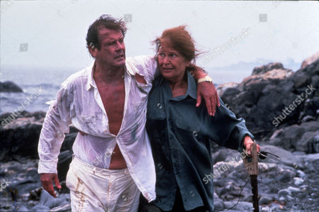 Stock Picture of FILM STILLS OF 'BED & BREAKFAST' WITH 1992, COLLEEN DEWHURST, ROBERT ELLIS MILLER, ROGER MOORE, SHIP WRECKED, OUTSIDE, DIRTY, INJURED, EXHAUSTED, HELPING, LEANING, BEACH, ISLAND, EXTERIOR IN 1992