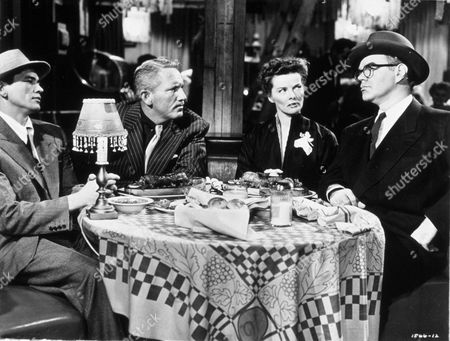 Stock Image of FILM STILLS OF 'PAT AND MIKE' WITH 1952, CHARLES BRONSON, DINING ROOM TABLE, KATHARINE HEPBURN, GEORGE MATHEWS, SPENCER TRACY, CROOKS, GANGSTER, TABLE, SITTING, DINING, HAT, HAT - MENS, GLASSES, LAMP IN 1952