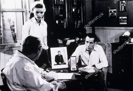 FILM STILLS OF 'KEY LARGO' WITH 1948, LAUREN BACALL, LIONEL BARRYMORE, HUMPHREY BOGART, DESK, OFFICE, MEETING, NEGOTIATING, BUSINESS, WORRIED, SERIOUS, FURROWED BROW, PICTURE, SITTING, EXPLAINING, CONCERNED, FROWN, HUNCHED OVER, SLOUCHING IN 1948