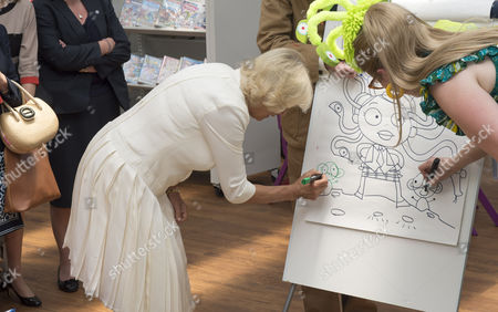 Camilla Duchess of Cornwall drawing a sea monkey with book illustrator Sarah McIntyre