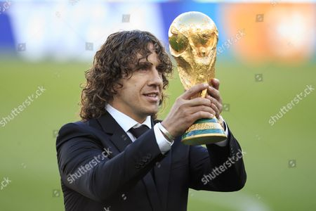 Carlos Puyol lifts the World Cup trophy before kick off