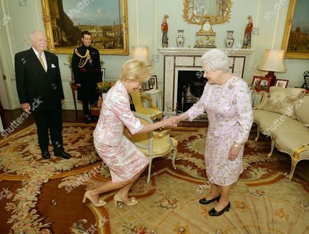 Queen Elizabeth II presents Dame Quentin Bryce, the outgoing Governor General of Australia the Insignia of Dame of the Order of Australia, watched by husband Michael Bryce