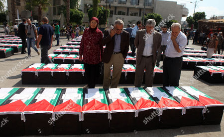 Stock Image of Former Palestinian Prime Minister Salam Fayyad (2nd left) looks on symbolic coffins during a protest in solidarity with Palestinians killed by Israeli forces in Gaza Strip