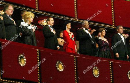 President George W Bush (R) and first lady Laura Bush (2nd R) sing the National Anthem with recipients of the 2002 Kennedy Center Honors, (L-R) conductor James Levine, Elizabeth Taylor, Paul Simon, Chita Rivera and James Earl Jones