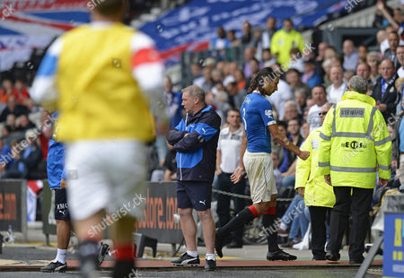 Bilel Mohsni of Rangers (R) trudges off past Ally McCoist manager of Rangers after being red carded