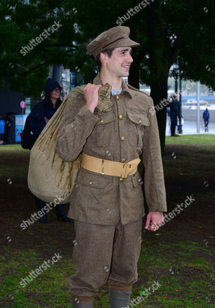 Stock Photo of Re-enactor Jack Monaghan watches on as Military Wives, Blake, Jonjo Kerr, perform and attend