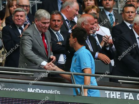 Former Arsenal assistant manager Pat Rice shakes hands with Samir Nasri of Manchester City as he collects his runners up medal